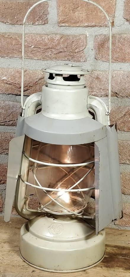 brandend witte stormlamp met schutkap van ALG uit frankrijk