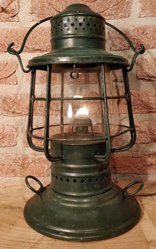 groene stormlantaarn met een raster om het glas met brandende vlam