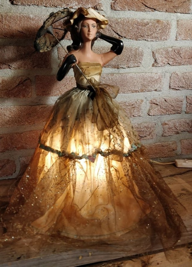victoriaanse lamp van vrouw in jurk waarbij de lamp onder de jurk zit