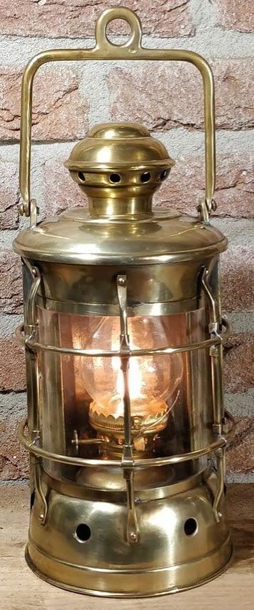 Een decoratieve scheepslamp van messing met brandende vlam