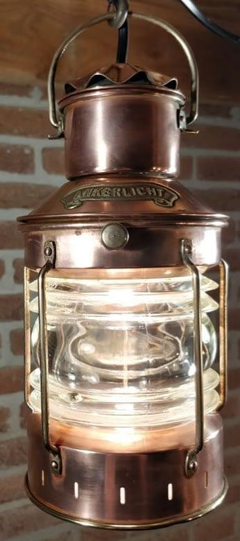 Decoratief ankerlicht welke hangt aan een haak. De lamp is van koper met details van messing