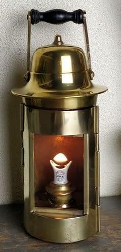 Prachtige kompaslamp van messing welke een porseleinen lonthouder heeft die u ziet branden.