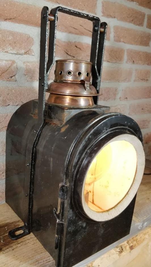 Brandende wagonlamp met koperen schoorsteen