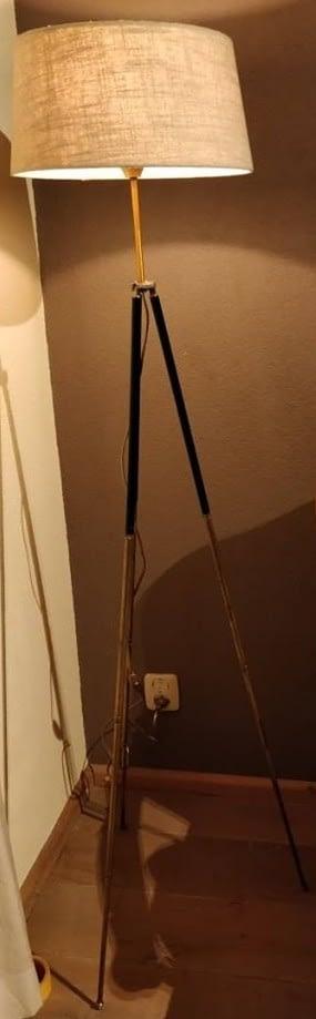 landelijk staande lamp waarvan de kap is geplaatst op een oud en messing fotostatief
