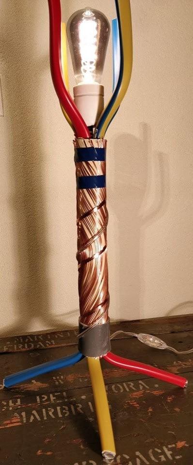 Aparte lamp welke gemaakt is van 3 180A stroomkabels met de kleuren blauw, geel en rood