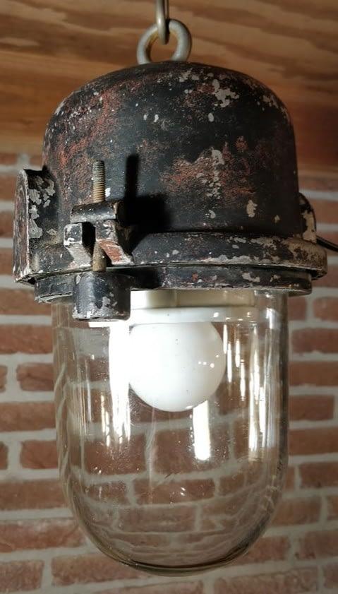 Bunkerlamp met dik glas hangend aan het plafon