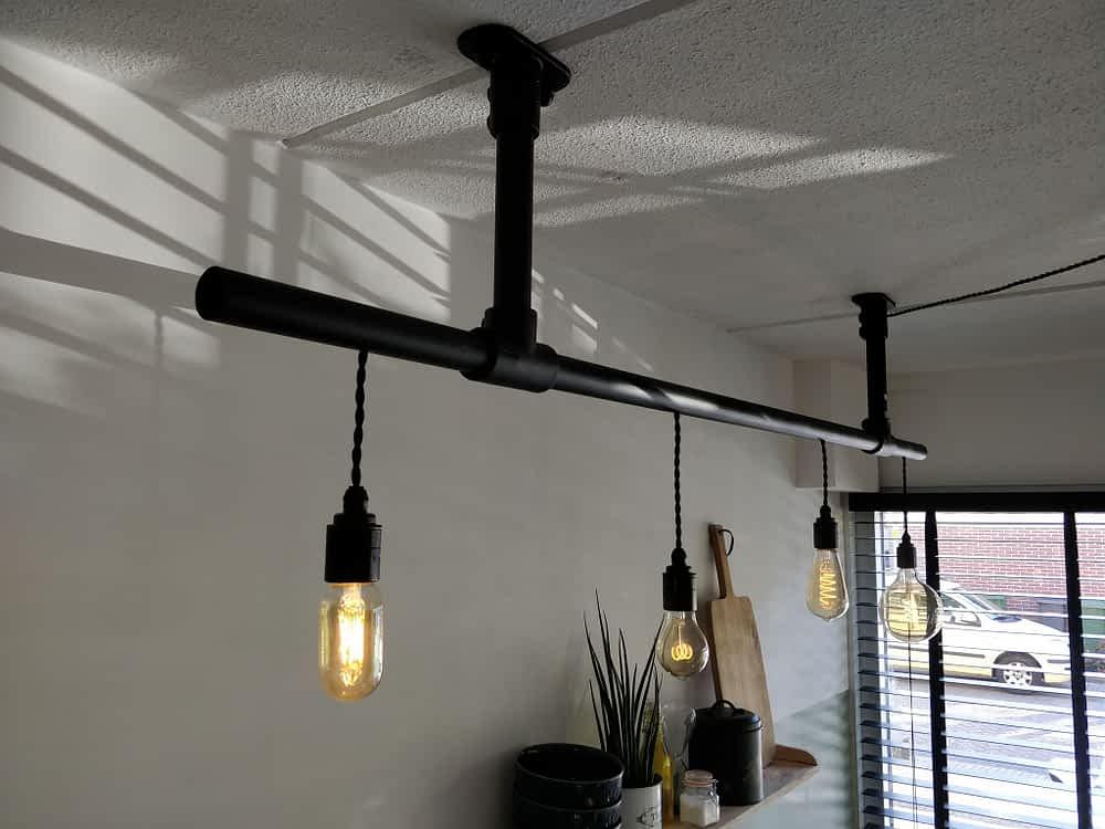 Zwarte steigerbuis lamp welke mooi boven een eettafel hangt