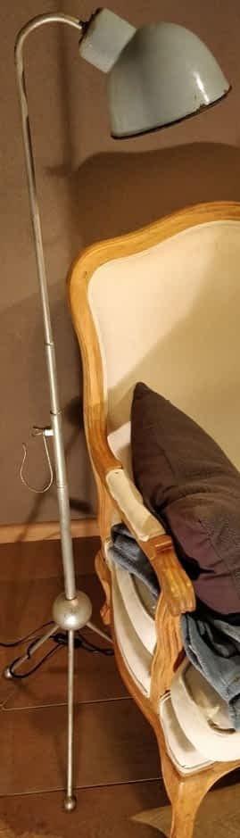 Staande lamp met emaille kap en bol in standaard naast een stoel