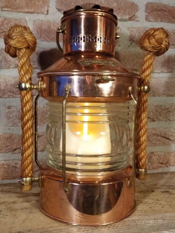 Scheepslamp met een kaars op batterij binnen in. Lamp is van koper met messing details en twee handvaten van touw aan de zijkanten