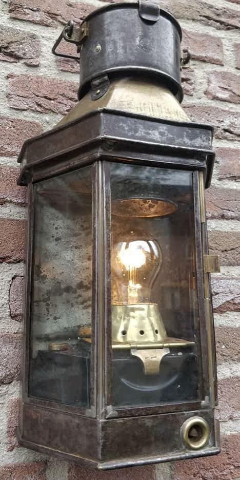Scheepslamp van Alderson Gyde hangend aan een muur met brandende lamp