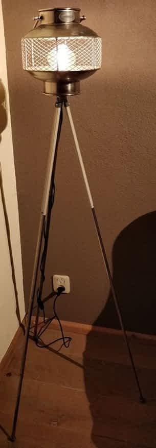 Staande lamp met een riverdale windlicht geplaatst op een oude camera statief